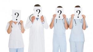 врачи держат знак вопроса перед лицом